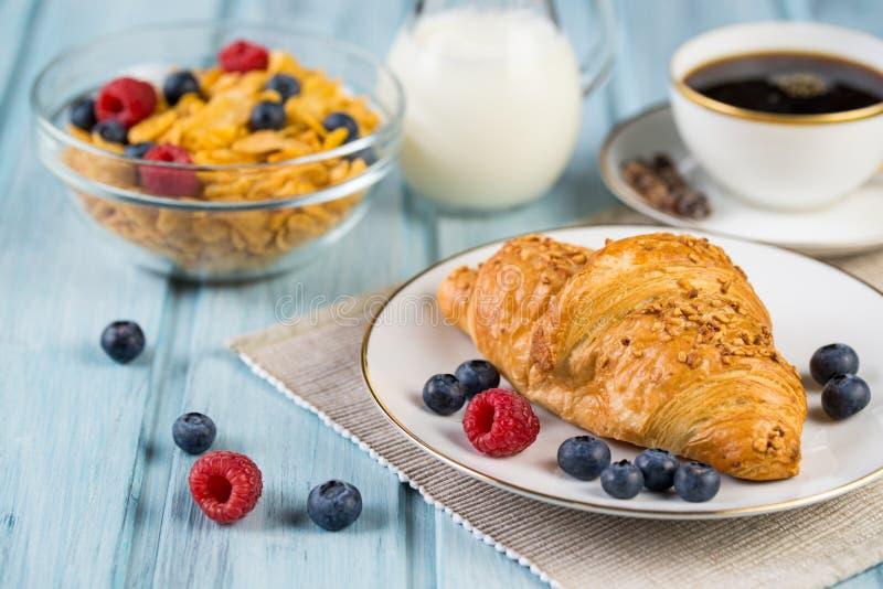 Ontbijt met croissant, graangewas, bessen en verse koffie royalty-vrije stock afbeelding