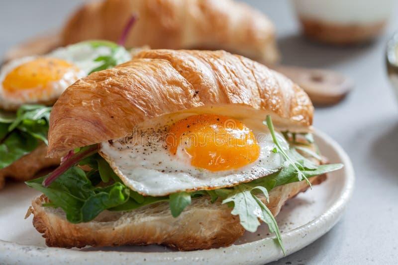 Ontbijt met Croissantsandwiches met Fried Egg, Saladebladeren en avocado royalty-vrije stock fotografie
