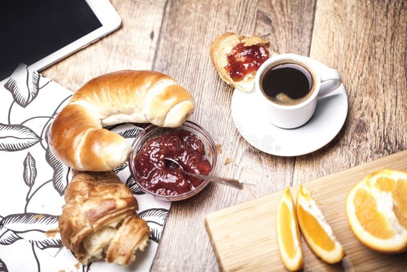 Ontbijt met een croissant en een koffie en sinaasappel stock afbeelding