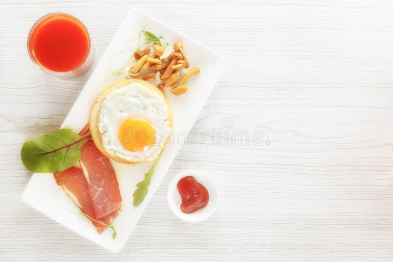 Ontbijt met gebraden ei op brood, bacon, paddestoelen, greens Saus en vers sap stock foto's