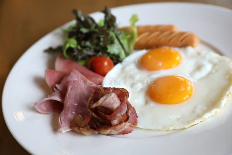Ontbijt met gebraden eieren, bacon, worsten, bonen, toosts, vers salade en fruit op houten lijst wordt geplaatst die royalty-vrije stock afbeeldingen
