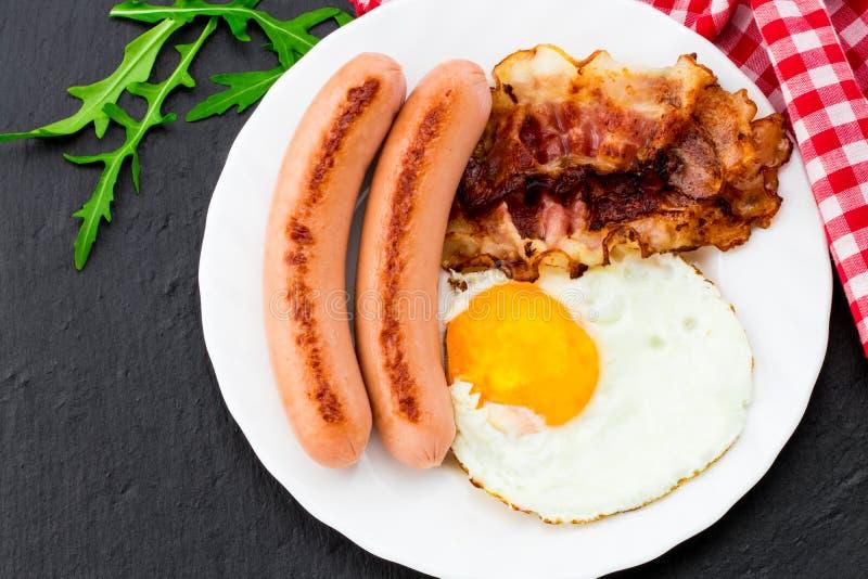 Ontbijt met gebraden eieren, bacon, worsten en plantaardige salade o royalty-vrije stock foto