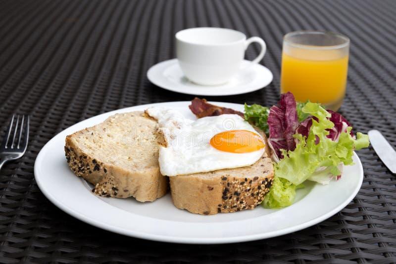 Ontbijt met gebraden eieren, groente, brood, koffie en sinaasappel wordt geplaatst die royalty-vrije stock foto