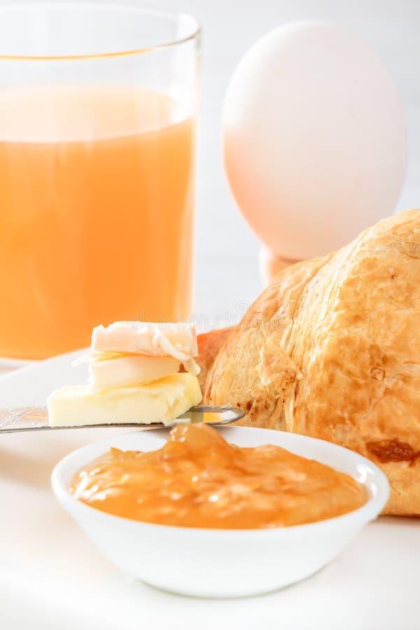 Ontbijt met gekookt ei, croissant met jam en vers gedrukt sap stock fotografie