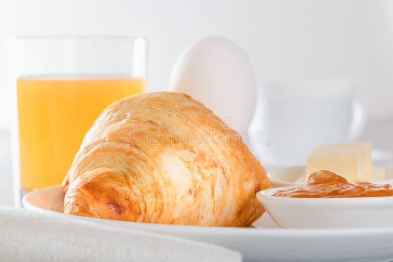 Ontbijt met gekookt ei, croissant met jam en vers gedrukt sap royalty-vrije stock foto's