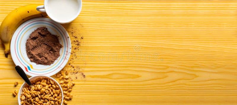 Ontbijt met graangewassen in een kom met melk, cacao en banaan stock afbeeldingen