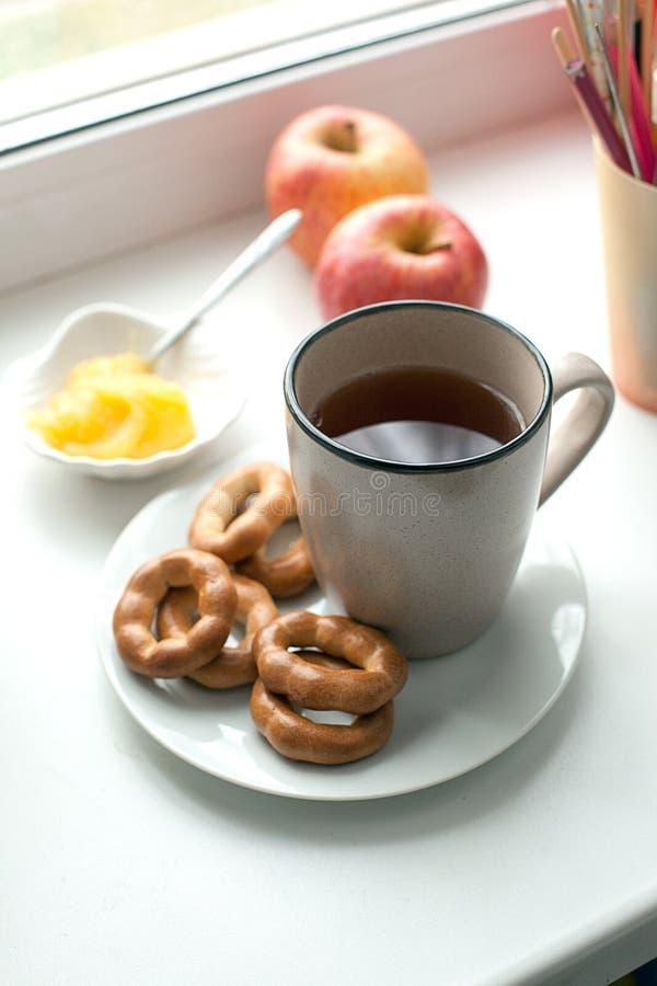 Ontbijt met hete thee, koekjes en honing Gezond huisontbijt cincept Sluit omhoog van een kop thee met koekjes op witte schotel royalty-vrije stock afbeeldingen