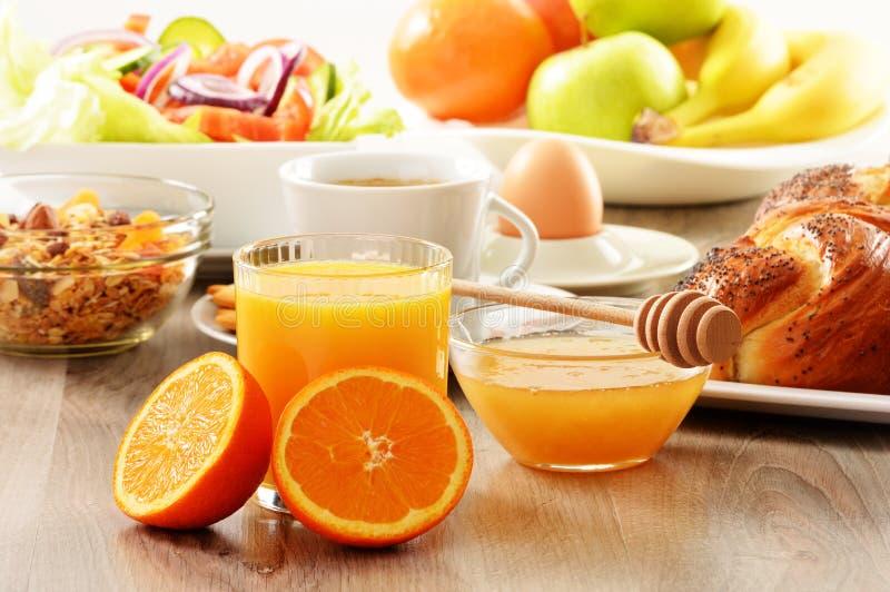 Ontbijt met inbegrip van koffie, brood, honing, jus d'orange, muesli stock foto