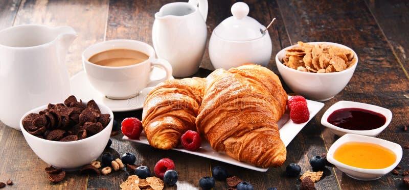 Ontbijt met koffie, croissants, graangewassen en vruchten wordt gediend die stock fotografie