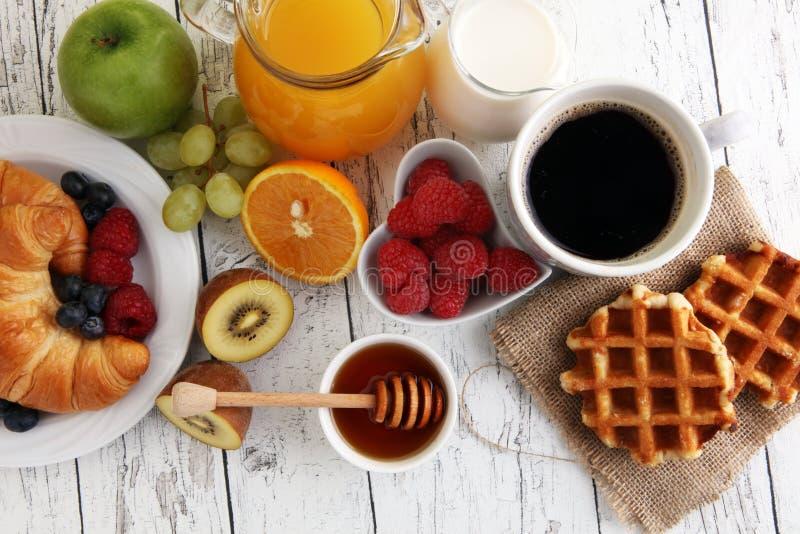 Ontbijt met koffie, jus d'orange, croissants en fruit wordt gediend dat stock afbeelding