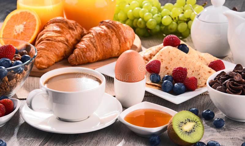 Ontbijt met koffie, sap, croissants en vruchten wordt gediend die stock afbeeldingen