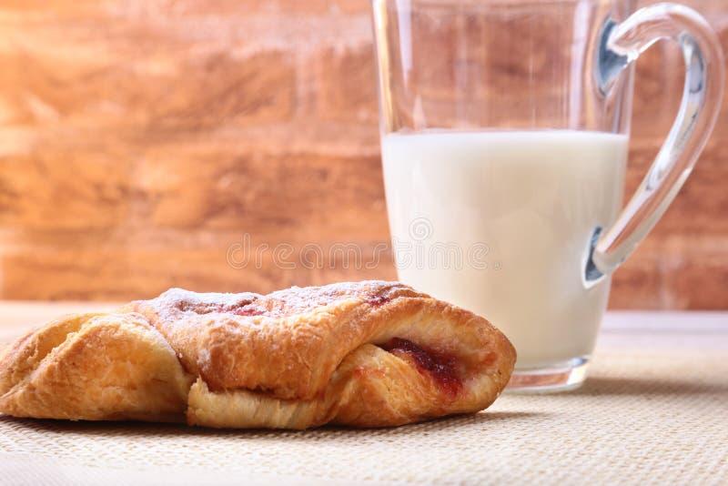 Ontbijt met traditioneel heet dwarsbroodje met jam en glas met melk op houten lijst Hoogste mening royalty-vrije stock foto's