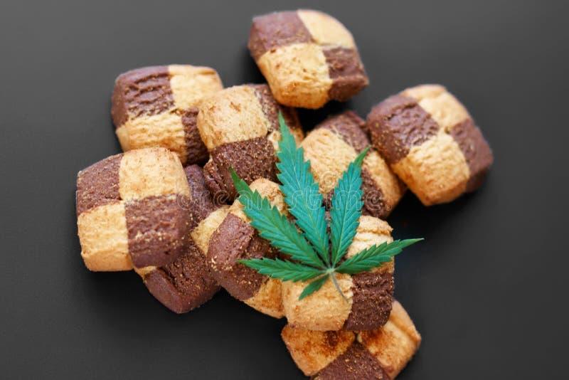 Ontbijt met zoete koekjes op een donkere achtergrond met een groen blad van cannabis Marihuanacbd dessert De ruimte van het exemp stock foto
