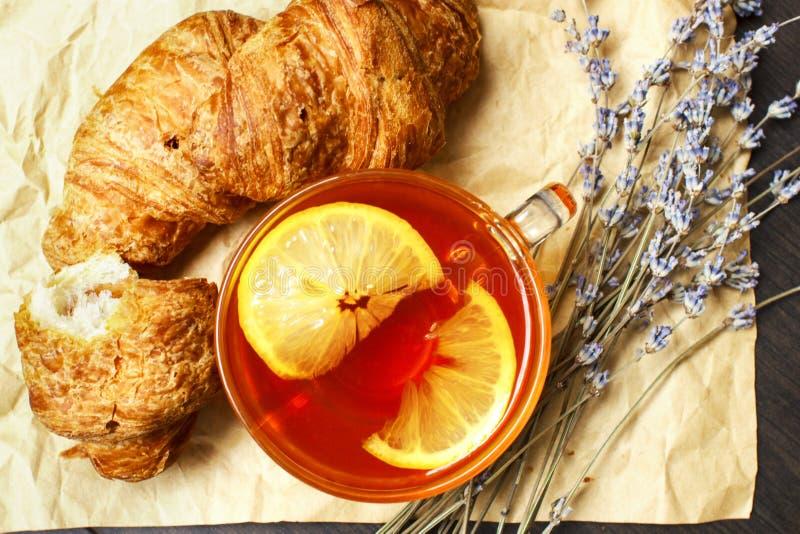 Ontbijt met zwarte hete thee en verse croissants op een document achtergrond met boeket van lavendel stock foto's