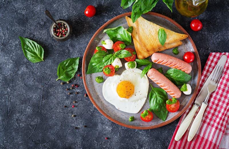 Ontbijt op de Dag van Valentine ` s - gebraden eieren in het vormhart, de worst, de toost en de caprese salade royalty-vrije stock afbeeldingen
