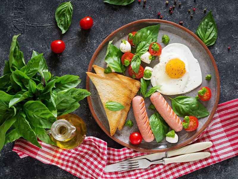 Ontbijt op de Dag van Valentine ` s - gebraden eieren in het vormhart, de worst, de toost en de caprese salade stock fotografie