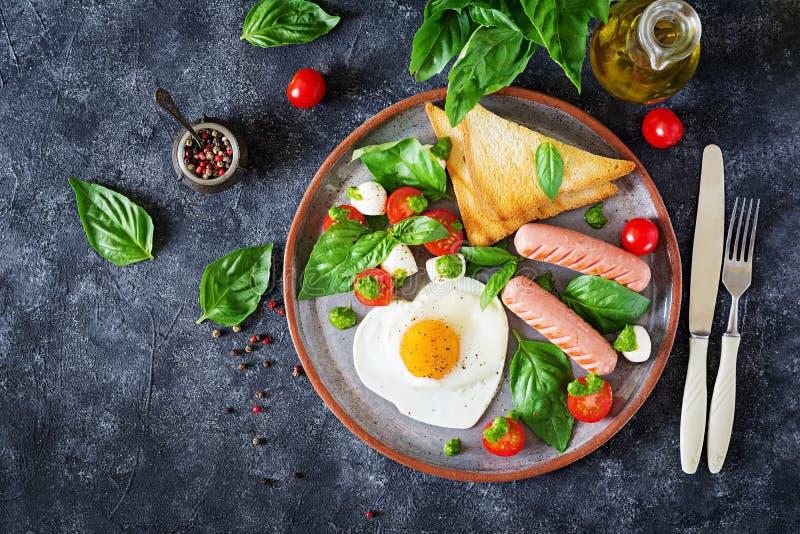 Ontbijt op de Dag van Valentine ` s - gebraden eieren in het vormhart, de worst, de toost en de caprese salade stock afbeeldingen