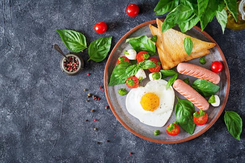 Ontbijt op de Dag van Valentine ` s - gebraden eieren in het vormhart, de worst, de toost en de caprese salade royalty-vrije stock afbeelding