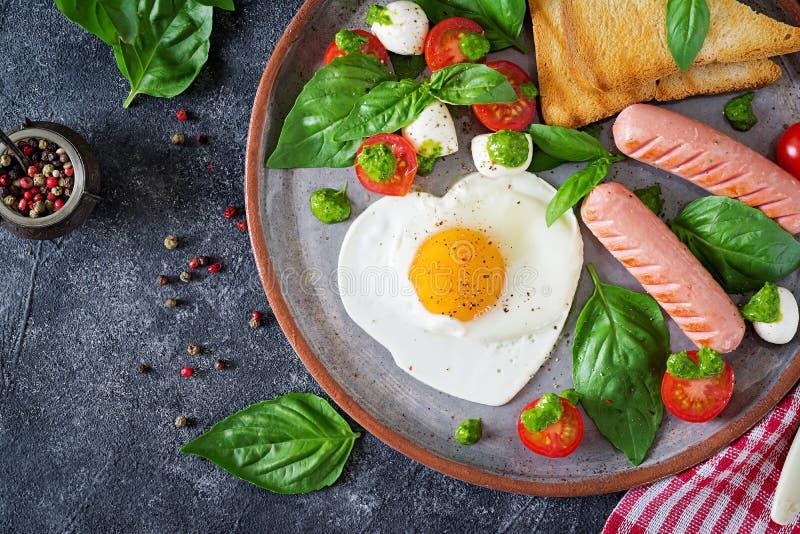 Ontbijt op de Dag van Valentine ` s - gebraden eieren in het vormhart, de worst, de toost en de caprese salade royalty-vrije stock foto's