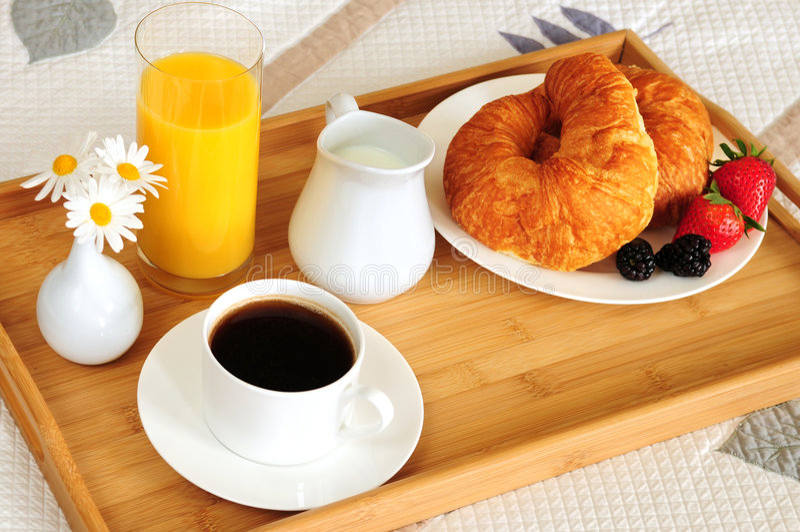 Ontbijt op een bed in een hotelruimte stock afbeeldingen