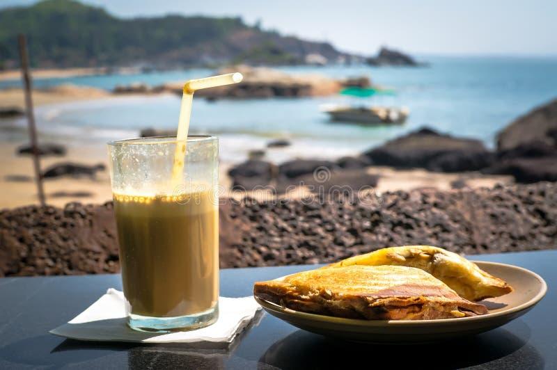 Ontbijt op het Strand Een sandwich en een koffiecocktail op de lijst in het restaurant op achtergrond van het overzees royalty-vrije stock foto's