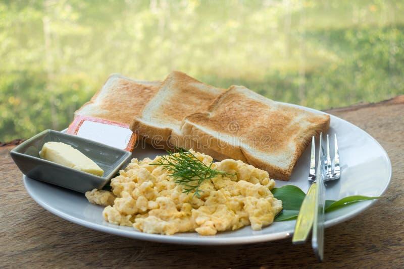 ontbijt & x28; Roereieren en bread& x29; met natuurlijke openluchtmening, stock fotografie
