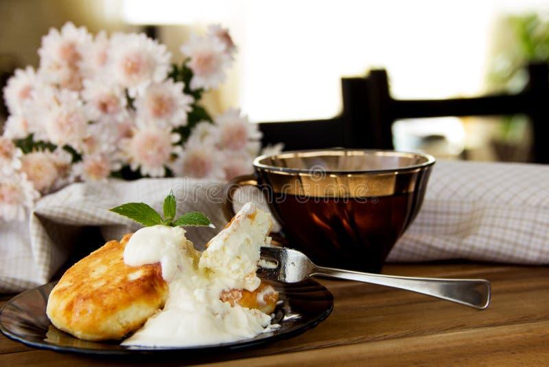 Ontbijt in Russische stijl - kaaspannekoeken met zure room en thee stock afbeeldingen