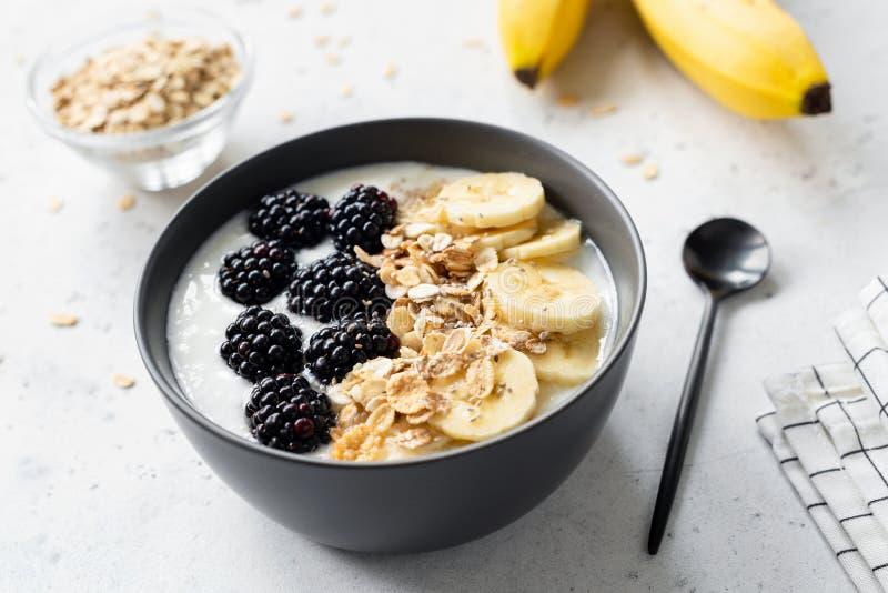 Ontbijt smoothie kom met banaan, granola en braambes royalty-vrije stock afbeeldingen