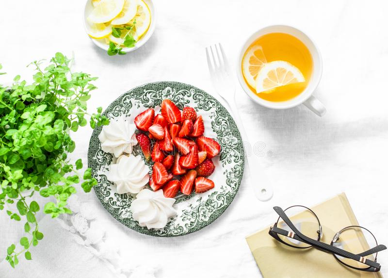 Ontbijt of snacklijst - verse aardbeien, schuimgebakje, groene thee met citroen Comfortabel huisstilleven op een lichte achtergro royalty-vrije stock fotografie