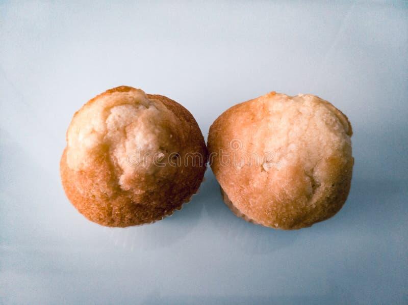Ontbijt twee cupcakes op een witte lijst stock foto