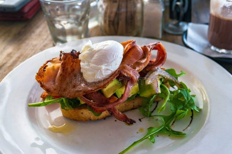 Ontbijt van bacon en gestroopt ei op toost met raket stock afbeeldingen