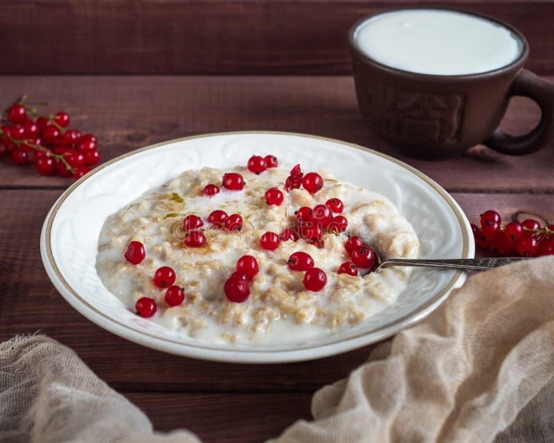 Ontbijt van de havermoutpap van de havermeelmelk met verse bessen van bes en melk, een lepel en een mok melk op een houten dienbl stock afbeelding