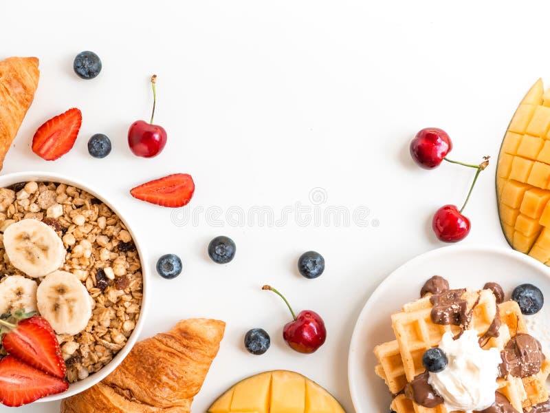 Ontbijtbessen en havermeelkader met exemplaarruimte Wafel met mango, croissant en kersen Vlak leg hoogste mening royalty-vrije stock foto's