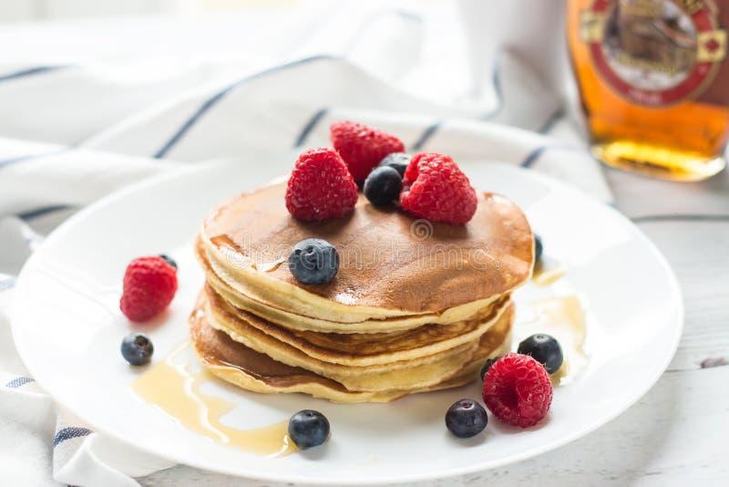 Ontbijtbessen Pannekoeken Romantisch ontbijt op een houten lijst De ochtend? gebied van de lente van groen gras en blauwe bewolkt stock afbeelding