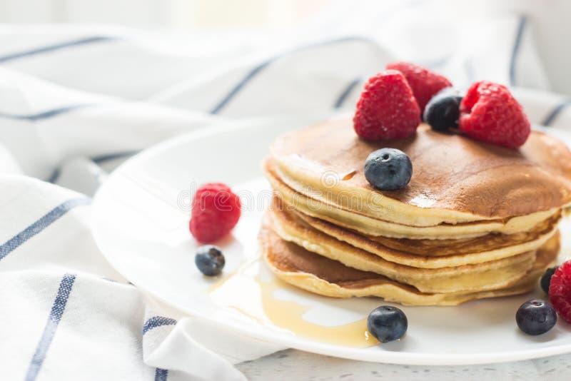 Ontbijtbessen Pannekoeken Romantisch ontbijt op een houten lijst De ochtend? gebied van de lente van groen gras en blauwe bewolkt royalty-vrije stock afbeeldingen