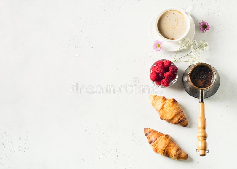 Ontbijtconcept met kop koffie, croissants, bessen en bloemen op witte achtergrond stock afbeelding