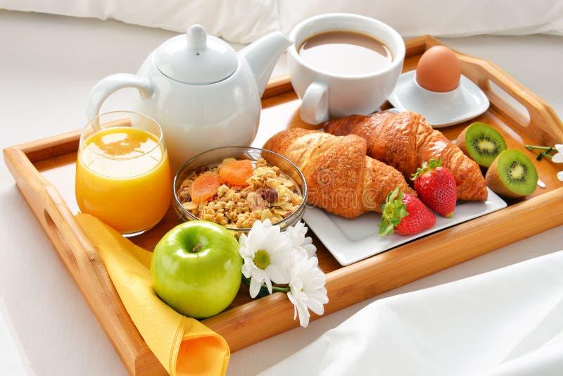 Ontbijtdienblad in bed in hotelruimte stock foto's