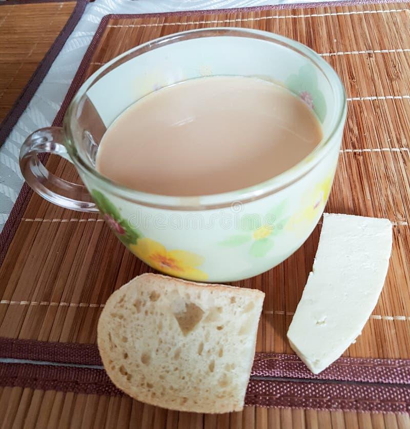 Ontbijtkoffie met melk in een glaskop, een brood, en een eigengemaakte kaas op de mat stock afbeelding