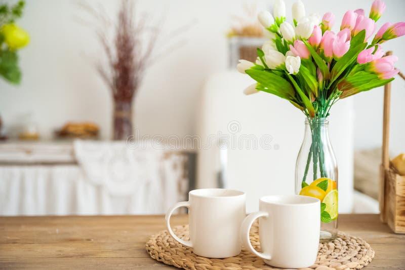 Ontbijtkoppen en fruit De lentetulpen op de lijst Houten lijst in een heldere rustiek-stijlkeuken Skandinavische stijl in int. royalty-vrije stock fotografie