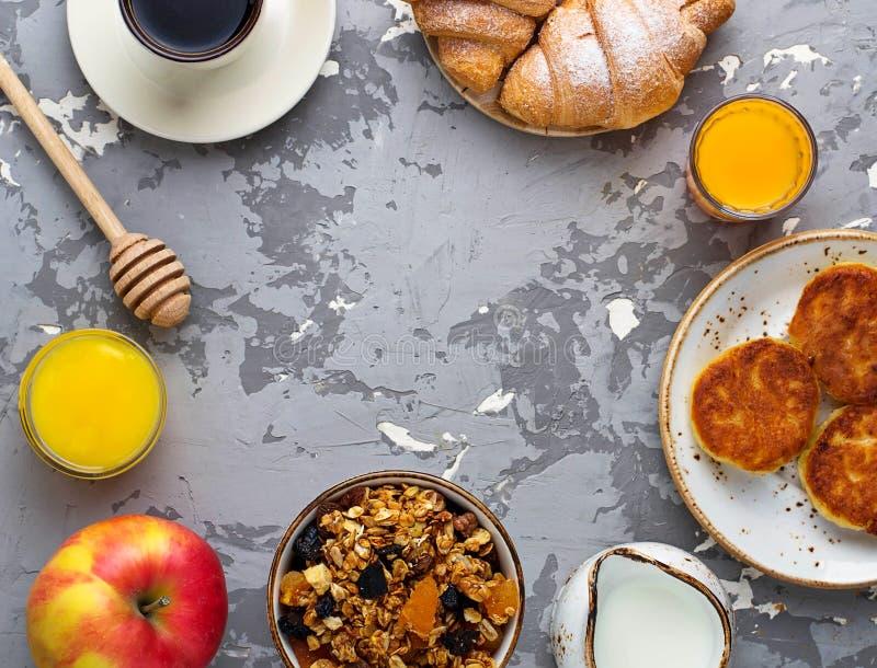 Ontbijtlijst met granola, croissants, appel, koffie, sap stock afbeelding