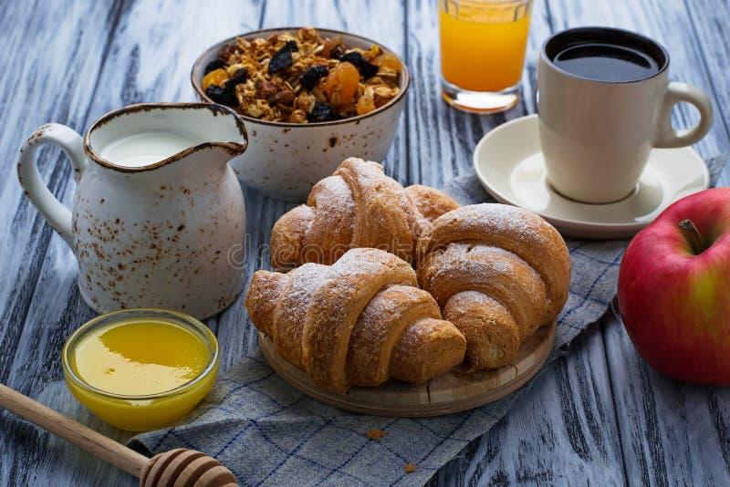 Ontbijtlijst met granola, croissants, appel, koffie, sap royalty-vrije stock fotografie