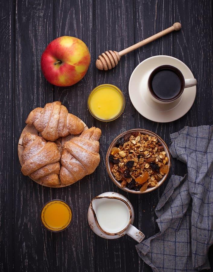 Ontbijtlijst met granola, croissants, appel, koffie, sap stock foto's