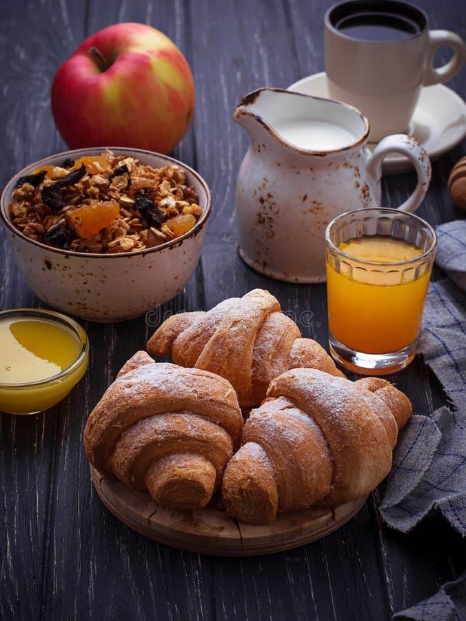 Ontbijtlijst met granola, croissants, appel, koffie, sap stock fotografie