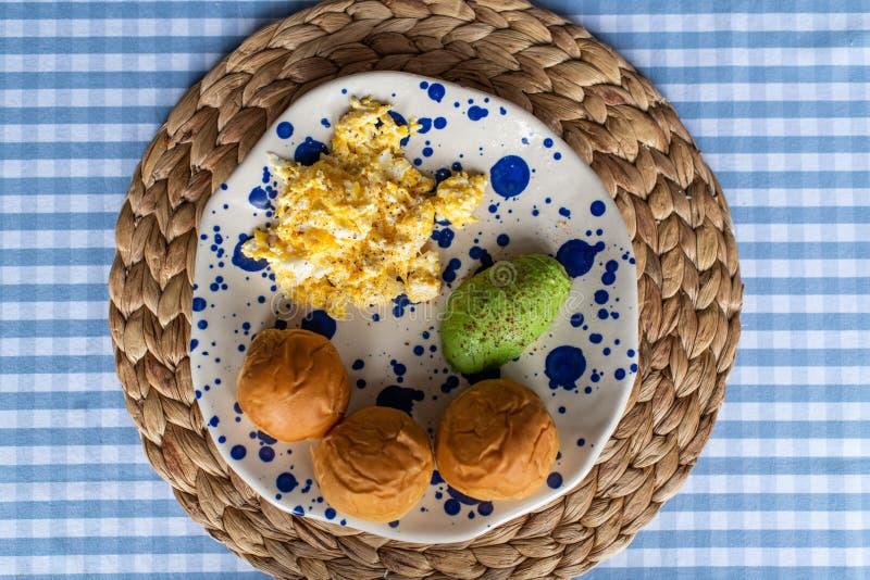 Ontbijtplaat van roereieren, gesneden avocado en klein sandwichbrood stock foto's