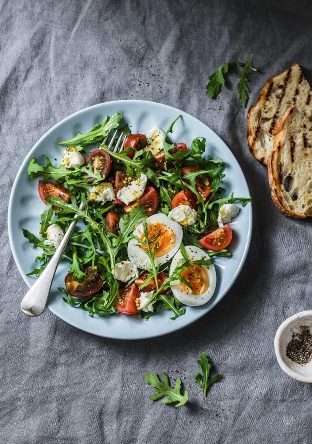 Ontbijtsalade - raket, kersentomaten, mozarella en gekookt ei met olijfolie, mosterd die, citroen zich op een grijze achtergrond  royalty-vrije stock foto's