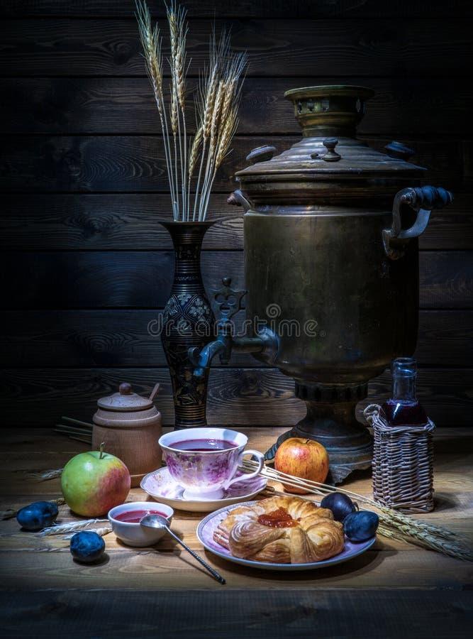 Ontbijtthee van een samovar met een kaastaart, een jam en bessen stock afbeelding