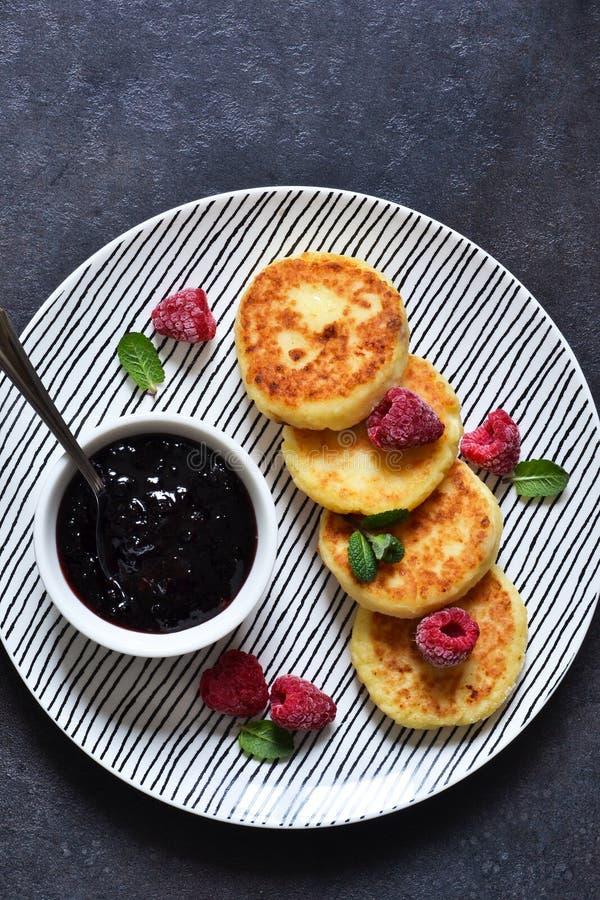 Ontbijttijd Kaascakes met frambozensaus voor ontbijt op de keukenlijst Mening van hierboven stock fotografie