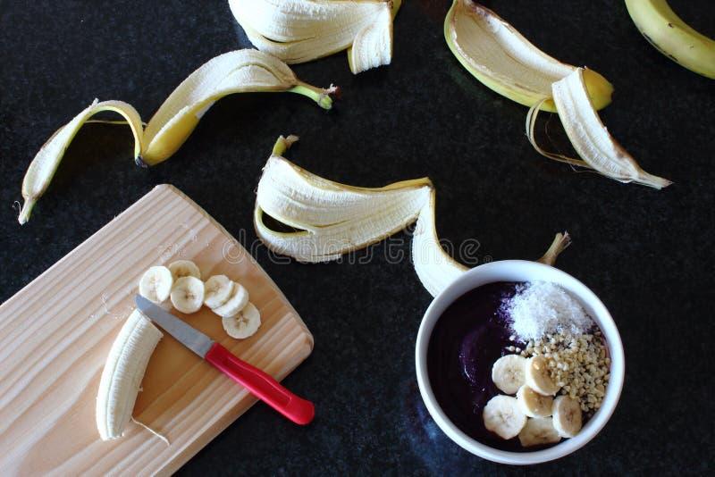 Ontbijtvoorbereidingen Hakkende banaan voor smoothiekom royalty-vrije stock afbeeldingen