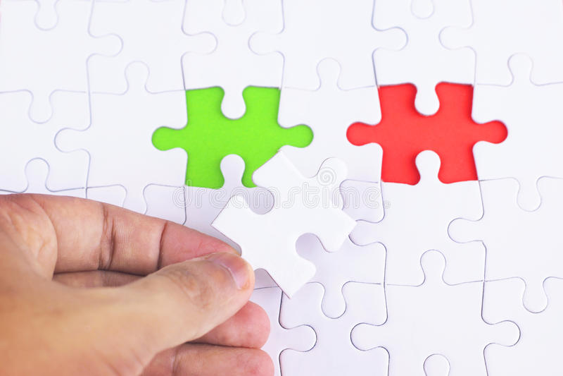 Ontbrekend puzzelstuk met groen en rood, bedrijfsconcept voor de voltooiing van het definitieve raadselstuk stock foto's