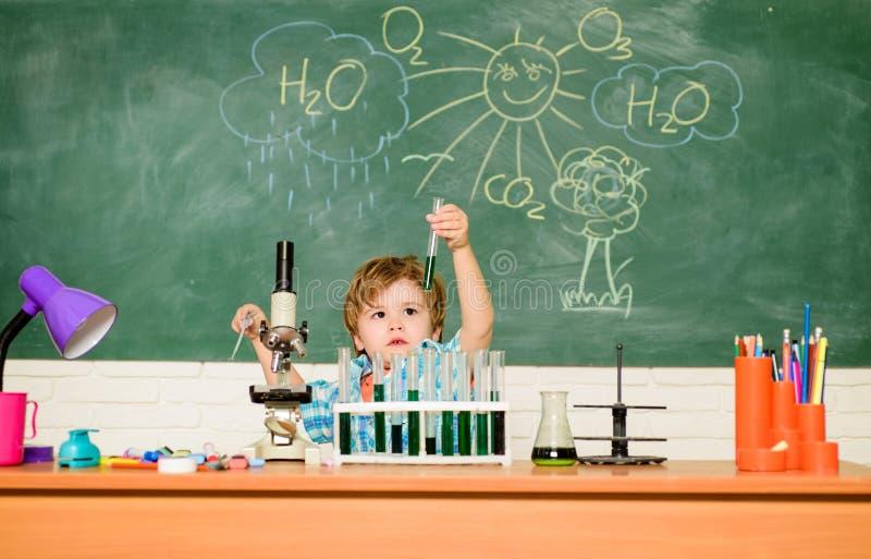 Ontdek vloeistoffen Studietoelagen en beurs Jongen die chemietest Wunderkind en vroege ontwikkeling uitvoeren klein royalty-vrije stock fotografie